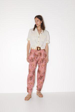 Zara Broek met tropical print op zijpand