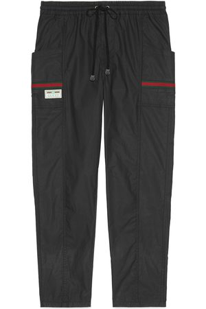 Gucci Coated cotton trousers with label